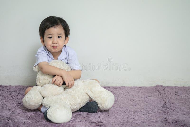 Il bambino asiatico del primo piano con il fronte dell'alesaggio con la bambola dell'orso si siede su tappeto con lo spazio della immagini stock libere da diritti