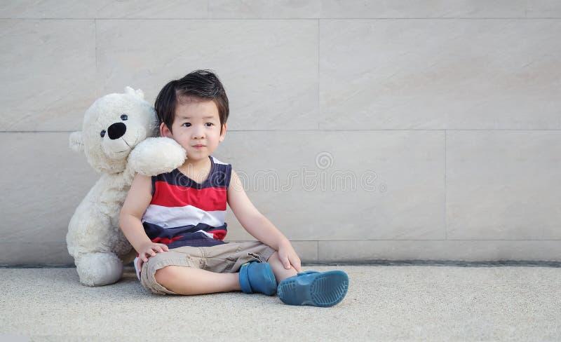Il bambino asiatico del primo piano con l'orso che la bambola si siede alla via sulla parete di pietra di marmo ha strutturato il fotografie stock