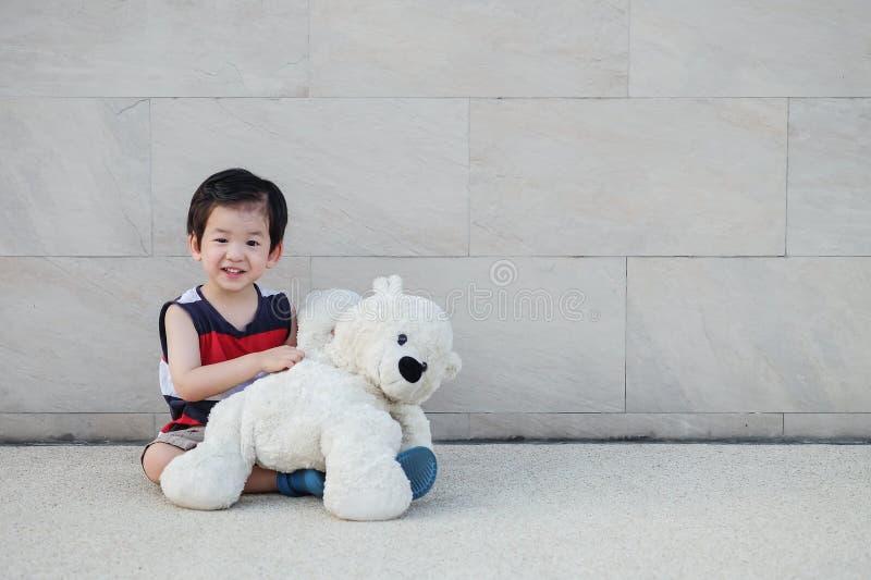 Il bambino asiatico del primo piano con l'orso che la bambola si siede alla via sulla parete di pietra di marmo ha strutturato il fotografia stock