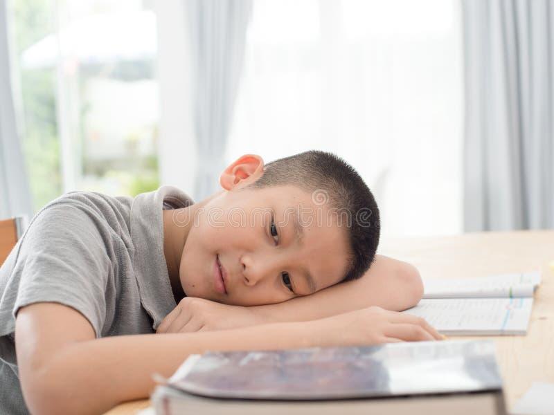Il bambino asiatico dell'età di scuola primaria fa il compito fotografie stock