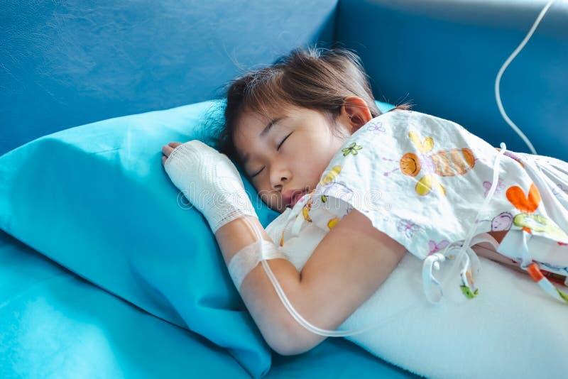 Il bambino asiatico di malattia ha ammesso in ospedale con il dispositivo di venipunzione salino a disposizione immagine stock libera da diritti