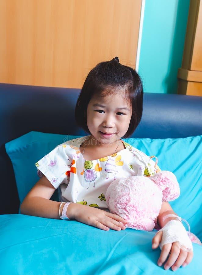 Il bambino asiatico di malattia ha ammesso in ospedale con il gocciolamento salino del dispositivo di venipunzione a disposizione fotografia stock libera da diritti