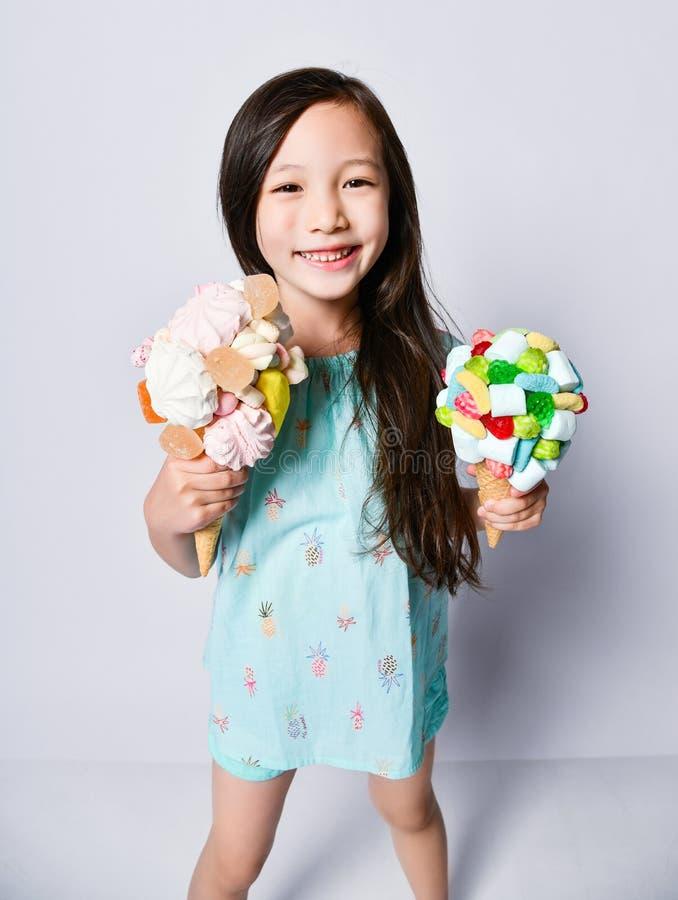 Il bambino asiatico divertente della neonata è soddisfatto di una coppia di grandi gelati in cialde che i coni con le guarnizioni immagini stock libere da diritti
