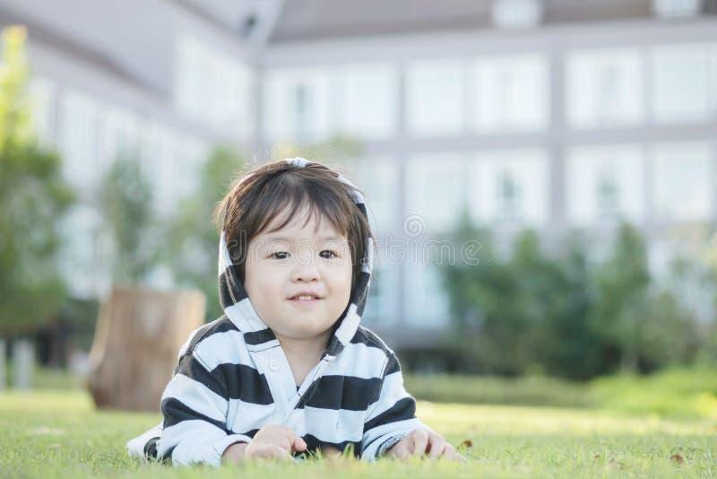 Il bambino asiatico felice del primo piano si è trovato sul pavimento dell'erba nei precedenti del giardino con moto sveglio immagini stock