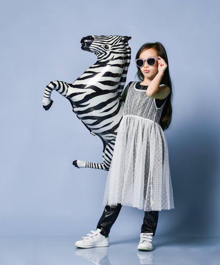 Il bambino asiatico fresco della neonata in vestiti ed occhiali da sole di alta moda fa un fronte kissy e le pose con il pallone  fotografia stock libera da diritti
