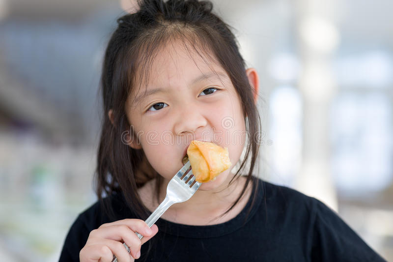 Il bambino asiatico gode di di mangiare l'alimento, Fried Spring Roll fotografia stock