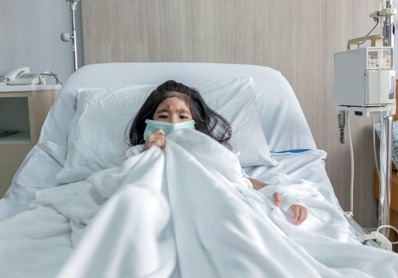 Il bambino asiatico paziente con la maschera ha febbre sul letto di ospedale immagine stock
