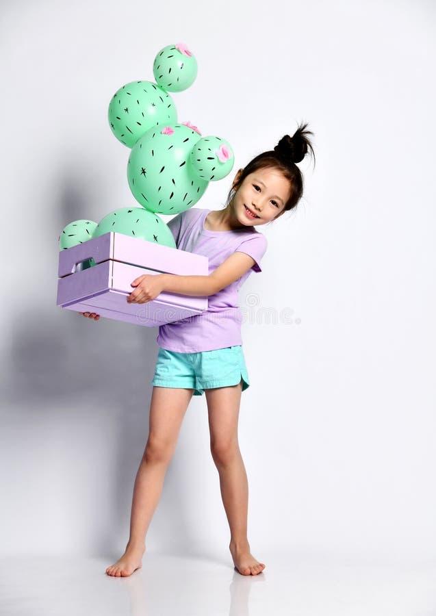 Il bambino asiatico sorridente della ragazza porta e dà una occhiata a fuori da dietro un contenitore di legno blu di fiore con u immagine stock