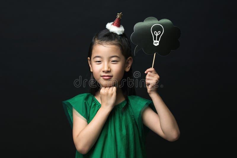 Il bambino asiatico sveglio della ragazza si è vestito in un vestito verde che tiene un bastone della lampadina di idea con una d immagine stock