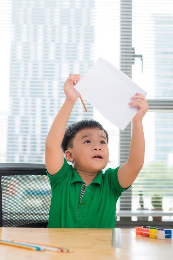 Il bambino asiatico sveglio si siede alla tavola con le cartelle variopinte e disegna fotografia stock libera da diritti