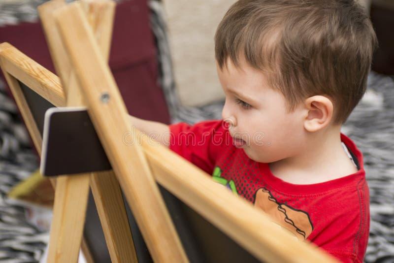 Il bambino attinge una lavagna fotografia stock libera da diritti