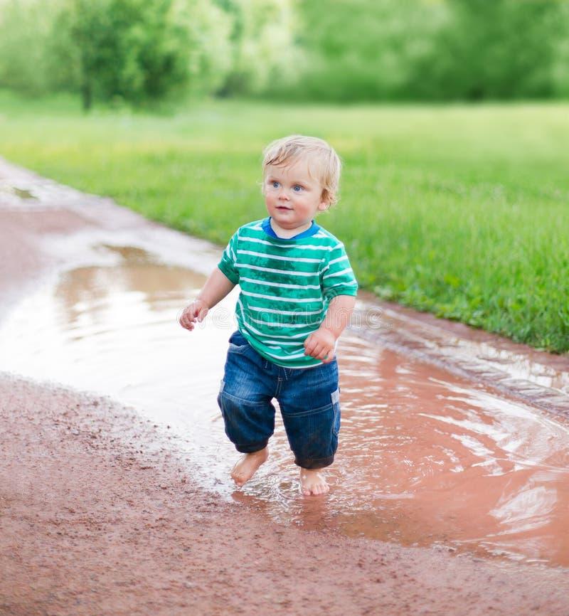 Il bambino cammina sulle pozze fotografia stock