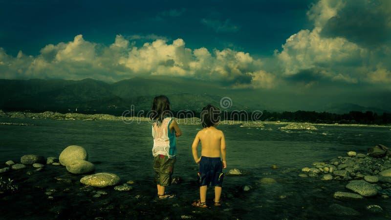 Il bambino in canottiera sportiva bianca accanto al bambino nel nero mette vicino al mare durante il giorno fotografia stock libera da diritti