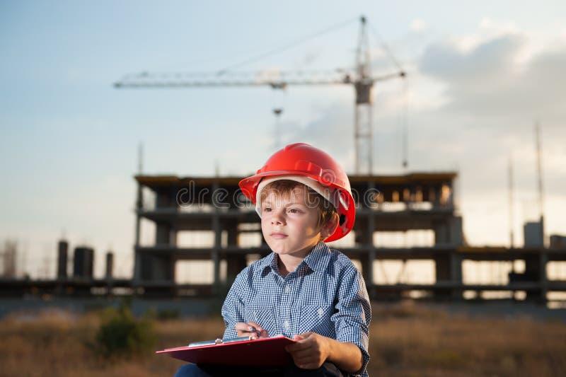 Il bambino in casco arancio fa le note su una compressa su un fondo della costruzione con una gru fotografia stock libera da diritti