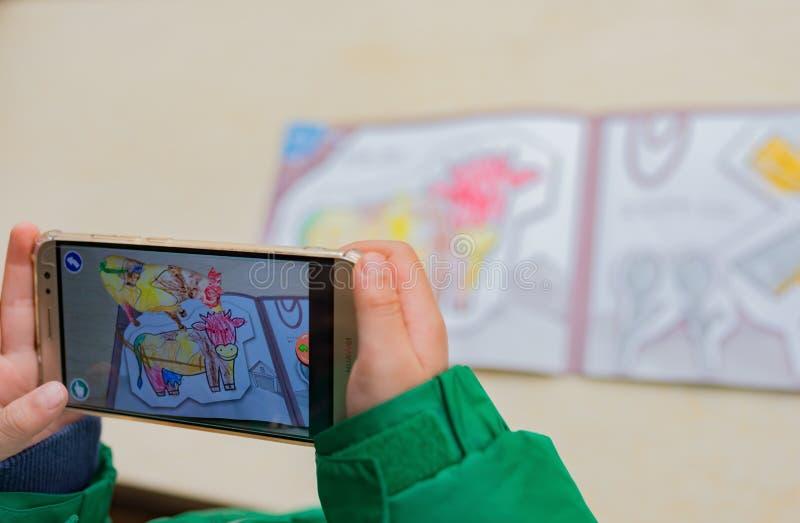 Il bambino che gioca le pitture a finestra aumentate della realtà di un colore ha riempito la mucca via il cellulare Giochi di VR fotografia stock libera da diritti
