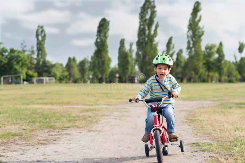 Il bambino che guida una bicicletta fotografia stock