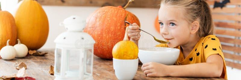 Il bambino che mangia la minestra della zucca in Halloween ha decorato la stanza dinning Fondo di stile di vita dell'alimento di  fotografia stock libera da diritti