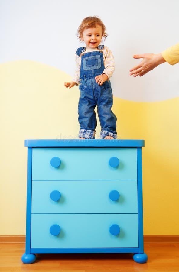 Il bambino che salta dall'armadietto immagini stock libere da diritti