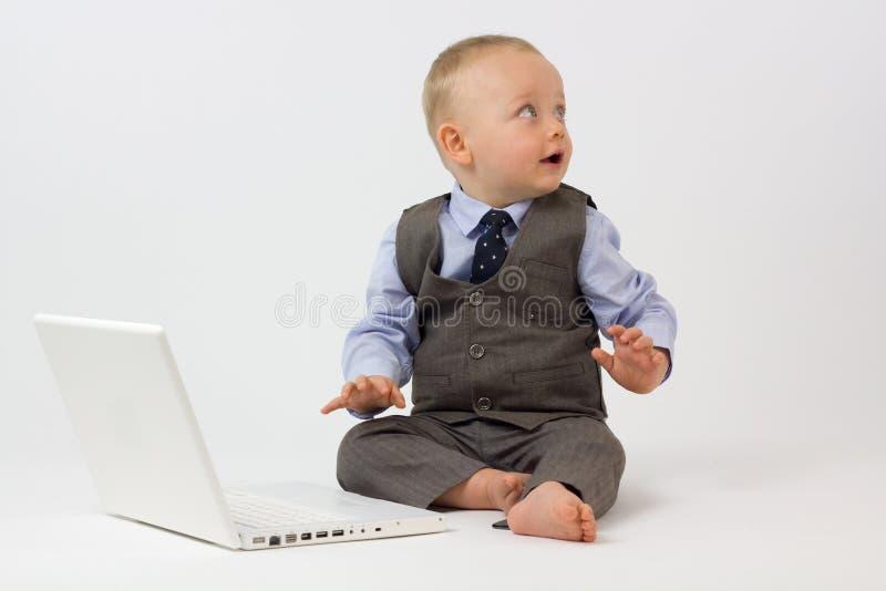 Il bambino con il computer portatile esamina lo spazio della copia immagine stock libera da diritti