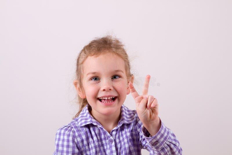 Il bambino con un sorriso mostra due dita immagini stock