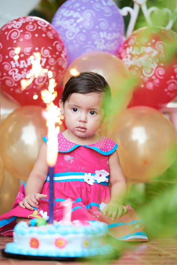 Il bambino considera la torta di compleanno fotografia stock