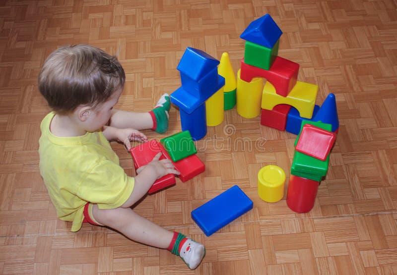 Il bambino costruisce un castello dal progettista di plastica Gioco con il progettista fotografia stock libera da diritti