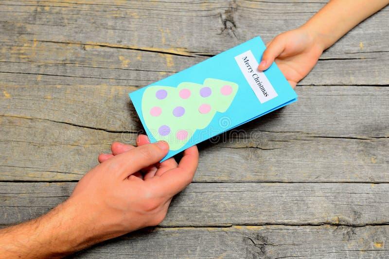 Il bambino dà una cartolina di Natale al papà Il piccolo bambino dà un regalo al padre I bambini passano ed uomini mano Buon Nata immagine stock libera da diritti