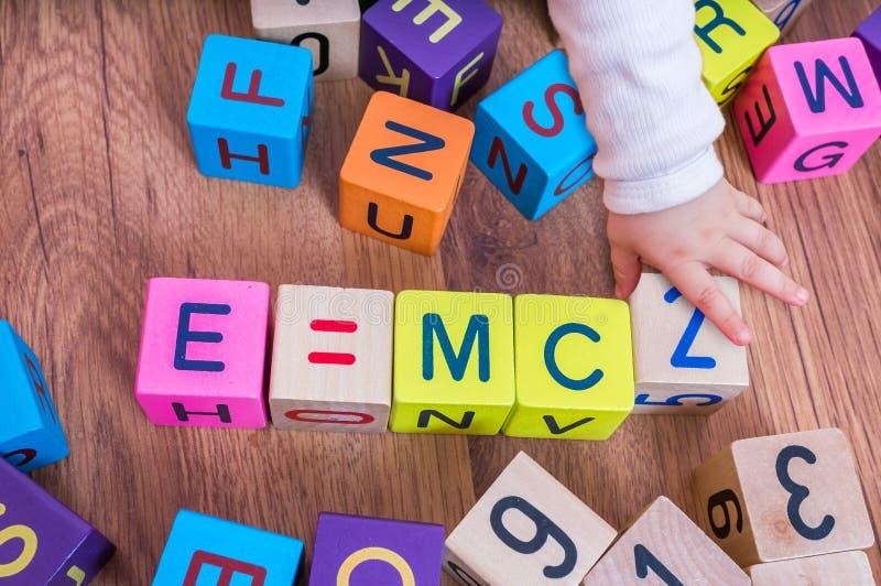 Il bambino del genio con alto quoziente d'intelligenza sta giocando con i cubi e sta scrivendo le formule fotografie stock libere da diritti