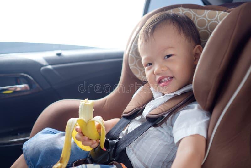 Il bambino del neonato del bambino che si siede nella tenuta del carseat della sicurezza & gode di di mangiare la banana fotografie stock libere da diritti
