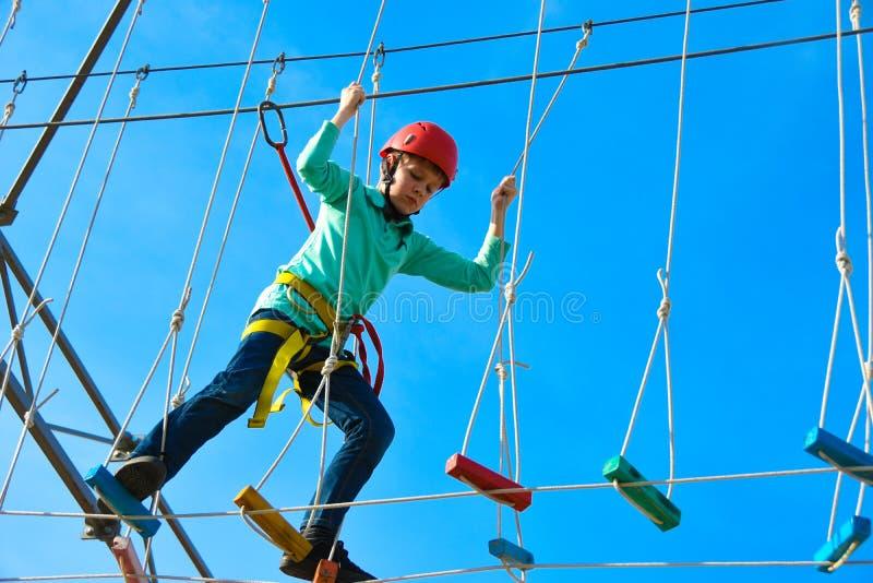 Il bambino del ragazzo fa un passo sui bordi di legno sulla corsa ad ostacoli in un parco di divertimenti, le attività all'aperto fotografia stock libera da diritti
