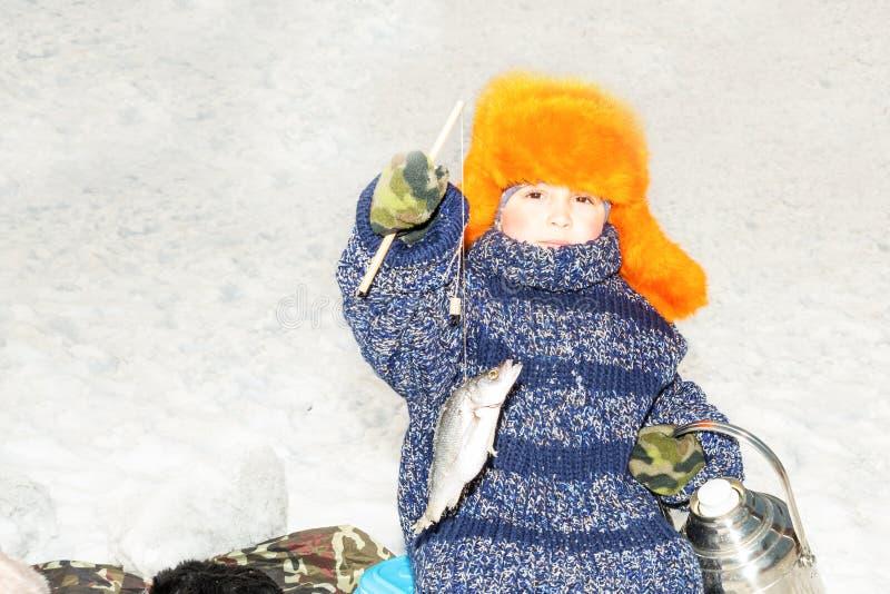 Il bambino del ragazzo ha pescato un pesce su un'esca sull'inverno di pesca Sport invernali e fresa fotografia stock