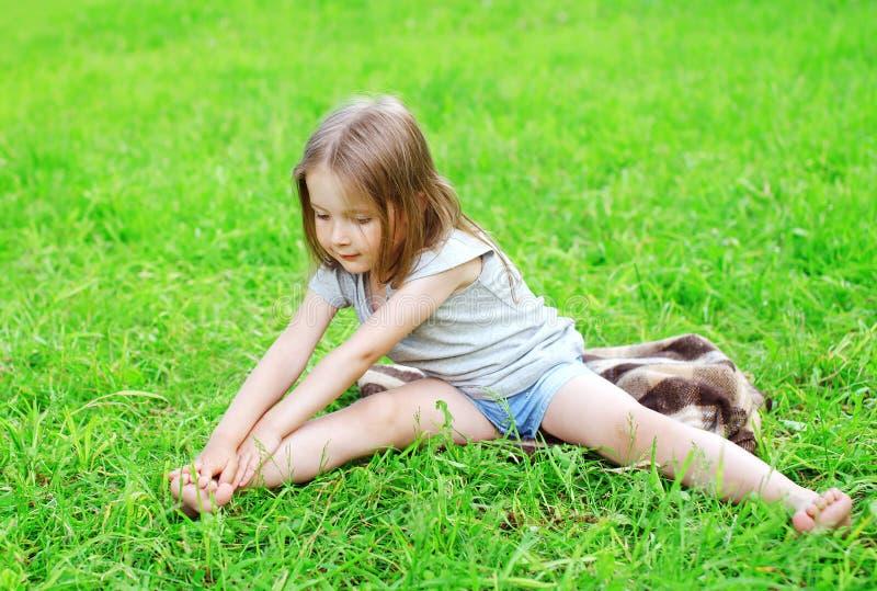 Il bambino della bambina che si siede sull'erba fa l'allungamento di yoga immagine stock