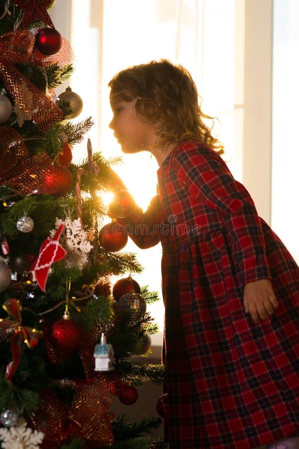 Il bambino della bambina decora un albero di Natale contro la finestra w fotografia stock