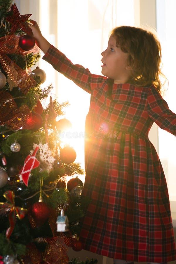 Il bambino della bambina decora un albero di Natale contro la finestra w fotografia stock libera da diritti