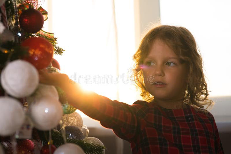 Il bambino della bambina decora un albero di Natale contro la finestra w immagine stock libera da diritti