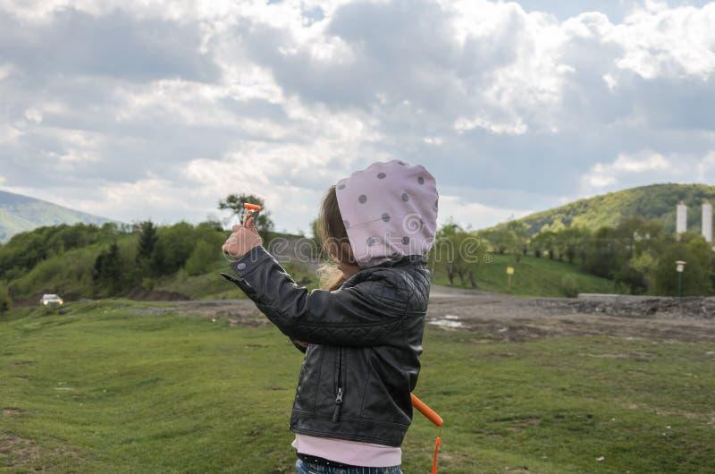 Il bambino della bambina prende le immagini sul telefono della montagna mentre viaggia fotografia stock libera da diritti