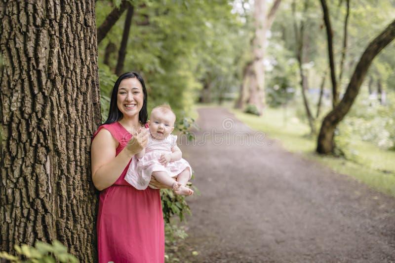 Il bambino della figlia e della madre nel prato dell'estate parcheggia immagini stock
