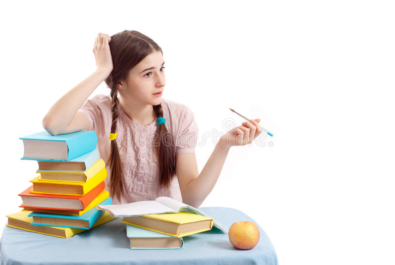Il bambino della ragazza alla tabella con i libri fotografia stock