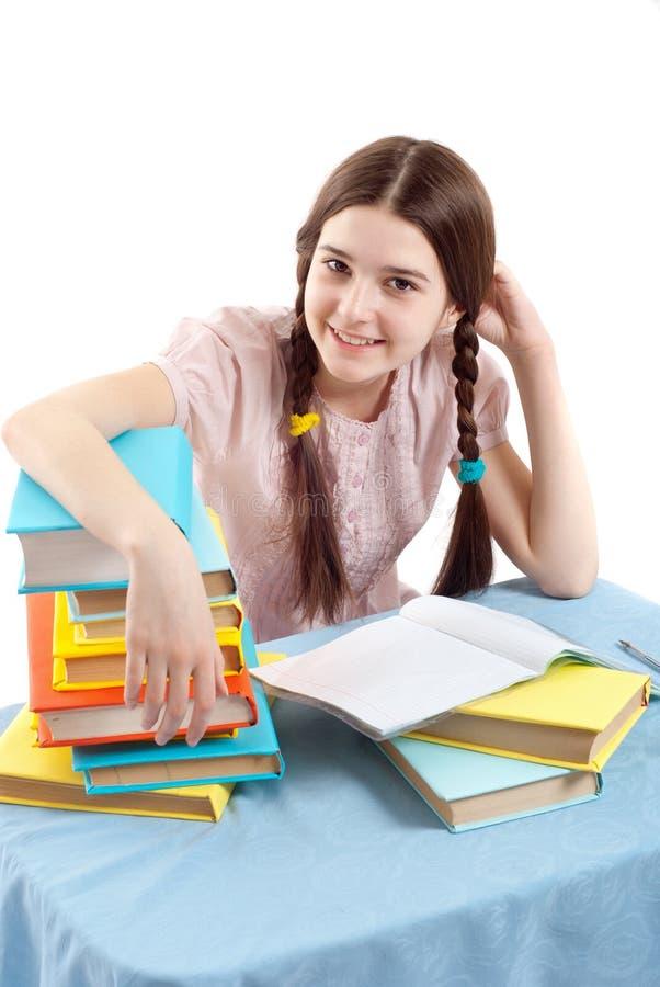Il bambino della ragazza alla tabella con i libri fotografia stock libera da diritti