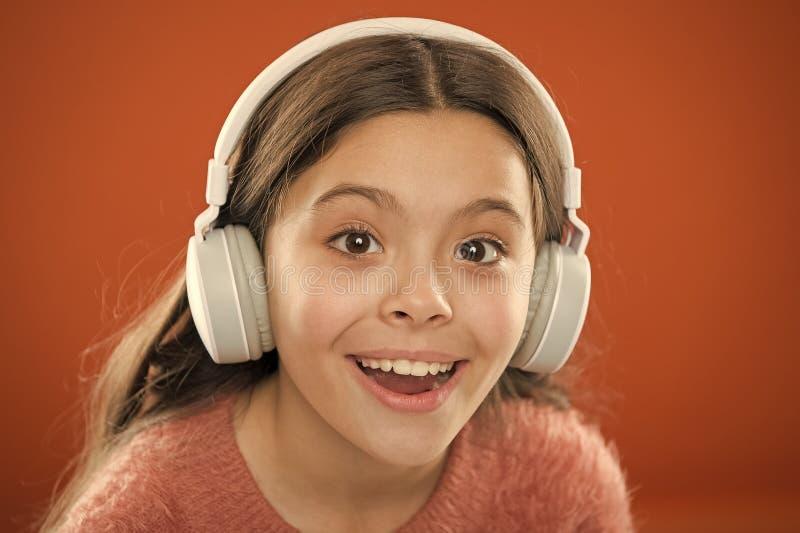 Il bambino della ragazza ascolta musica che le cuffie moderne si chiudono su Ottenga la sottoscrizione di musica Access a milioni immagine stock libera da diritti