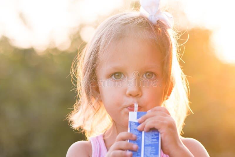 Il bambino della ragazza beve il succo immagini stock