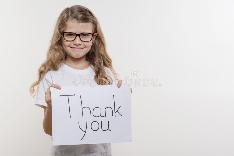 Il bambino della ragazza che tiene pezzo di carta con una parola VI RINGRAZIA Bakgrounde bianco fotografia stock libera da diritti
