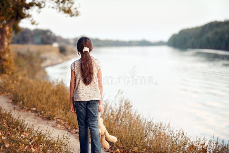 Il bambino della ragazza con l'orso del giocattolo che cammina lungo il percorso nella foresta al tramonto, al bello fiume ed al  fotografie stock libere da diritti