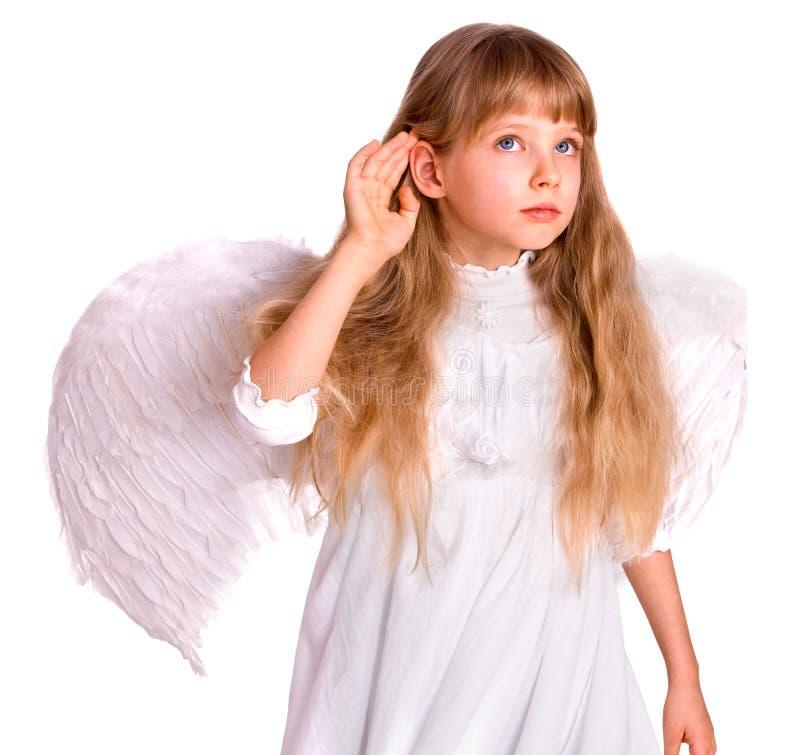 Il bambino della ragazza in costume di angelo ascolta, passa vicino all'orecchio. fotografia stock