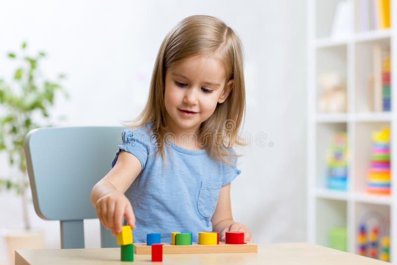 Il bambino della ragazza del bambino che gioca con il selezionatore gioca in scuola materna immagine stock