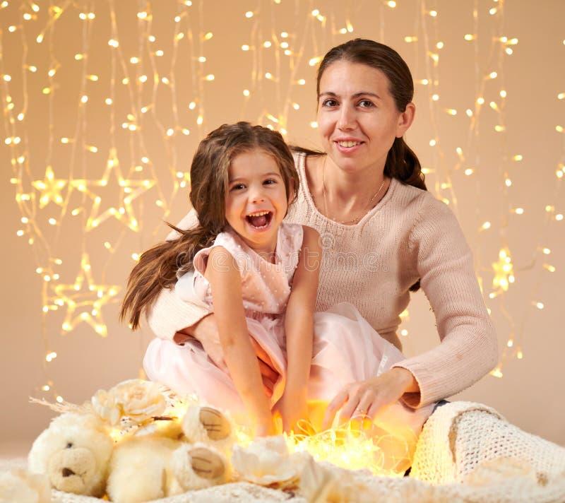 Il bambino della ragazza e della madre sta posando alle luci di natale, fondo giallo immagini stock