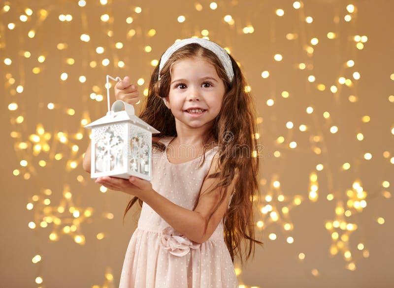Il bambino della ragazza sta posando con la lanterna alle luci di natale, il fondo giallo, vestito rosa immagini stock libere da diritti