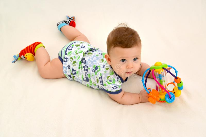 Il bambino di sei mesi tiene un giocattolo su un fondo leggero, la vista superiore fotografia stock