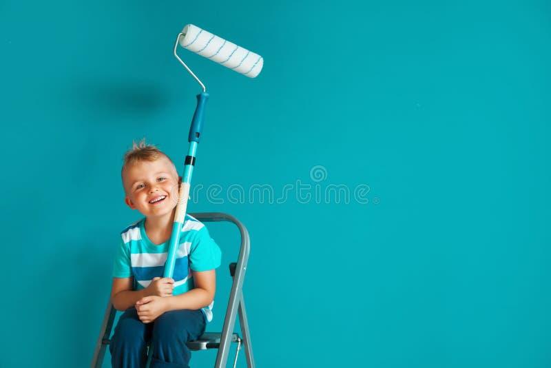 Il bambino dipinge la parete blu con un rullo Il ragazzo tiene una La fotografie stock