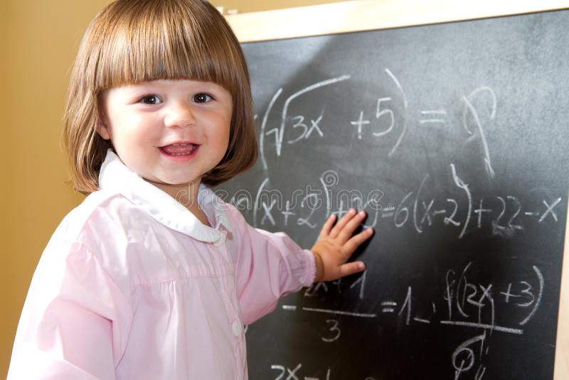 Il bambino disegna con gesso sulla lavagna fotografia stock